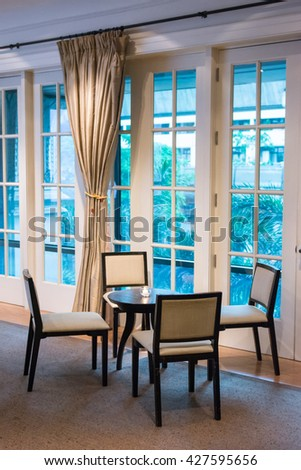 dining table and comfortable chairs in modern home with elegant table setting. Design in luxury room. Image have worm light in luxury room and selective focus - stock photo