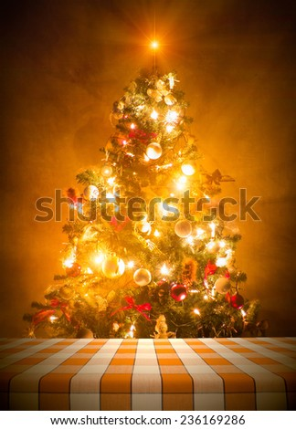 Dining table cloth against lit christmas tree - stock photo