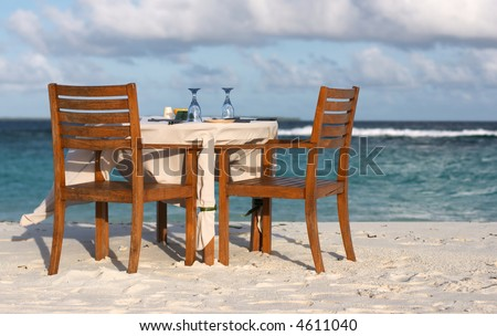 Dining table prepared for two on white sand beach close to the ocean - stock photo