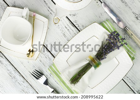 Dining table setting with lavender flowers on wooden table background - stock photo