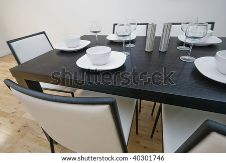 dining table setup with white leather chairs - stock photo