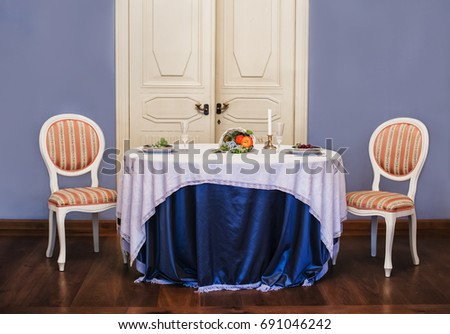 Dining Table With Appliances And Two Chairs Next To Each Other