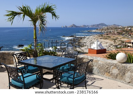 Dining tables with a great view of the Cabo San Lucas and Lands End in the far background - stock photo