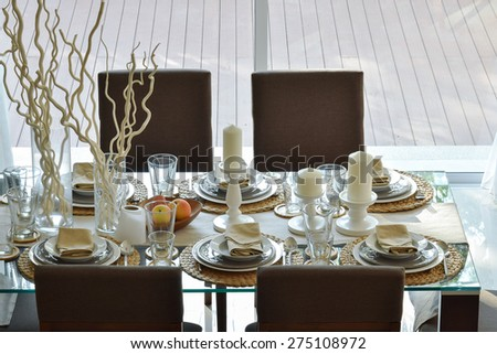 dining wooden table and comfortable chairs in modern home with elegant table setting - stock photo