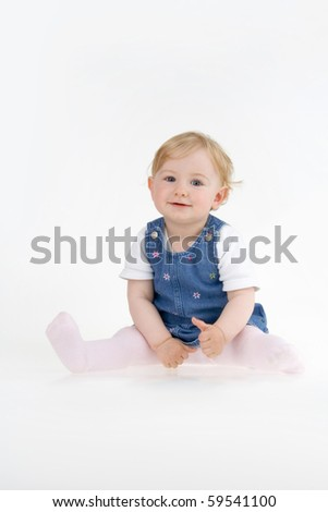 Dinky little girl sitting on white background.