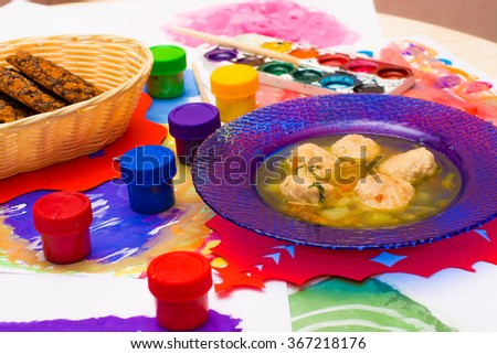 Dinner artist. Soup with meatballs and oatmeal cookie on the table of illustrations from a watercolor painting and watercolor palette and container