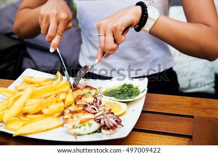 Dinner at restaurant. Woman eating seafood dish at a restaurant for lunch. Close up of hands and fresh fried calamari with fries. Slovenian, Italian, Croatian - Istrian traditional seafood dish.