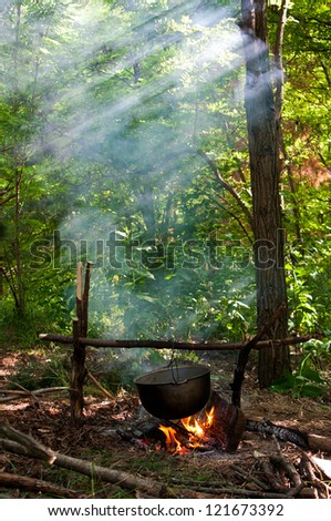 Dinner cooks in a large pot over an open fire - stock photo