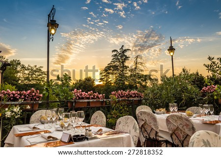 Dinner in Italian restaurant on the hills of Dozza (Bo): red, yellow and pink flowers with green leaves in pots.  Pink napkins and tablecloth, classy set of silver cutlery and crystal glasses - stock photo