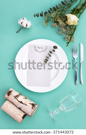 Dinner menu for a wedding or luxury evening meal. Table setting from above. Elegant empty plate, cutlery, glass and flowers. - stock photo