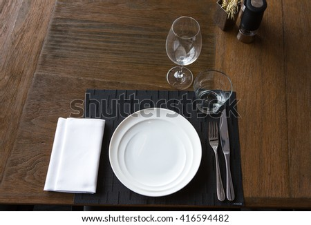 Dinner place setting. A white plate with silver fork and Wine glasses isolated on wood table. top view - stock photo