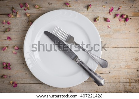 Dinner place setting - plate of white porcelain, fork and knife on white, old, wooden table - stock photo