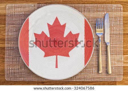 Dinner plate with the flag of Canada on it for your international food and drink concepts. - stock photo