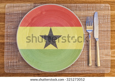 Dinner plate with the flag of Ghana on it for your international food and drink concepts. - stock photo