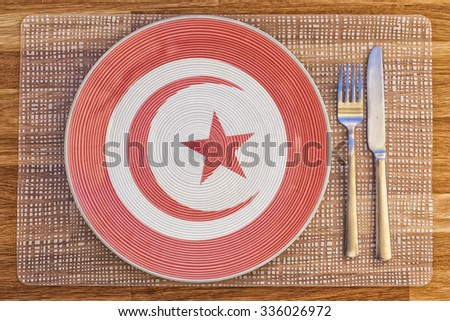Dinner plate with the flag of Tunisia on it for your international food and drink concepts. - stock photo