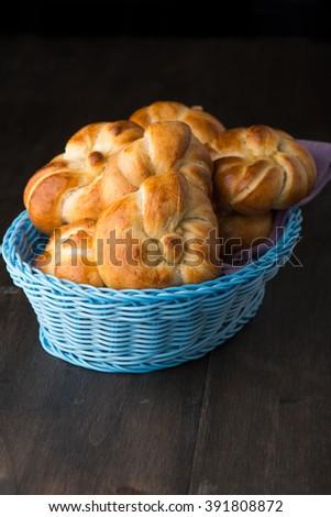 Dinner rolls in a blue basket on black background - stock photo