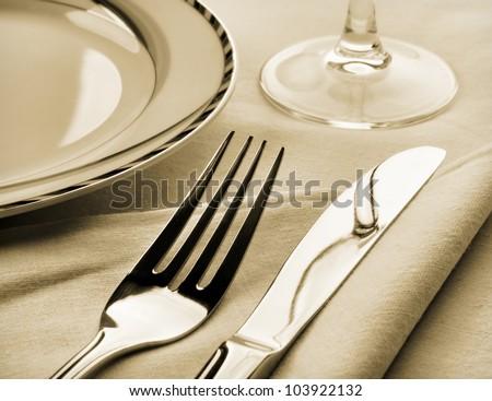 Dinner set. Fork and knife on napkin. Sepia toned - stock photo