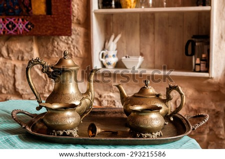 Dinner set of dishes for coffee and tea from the old bronze bell on the tray with the call for workers