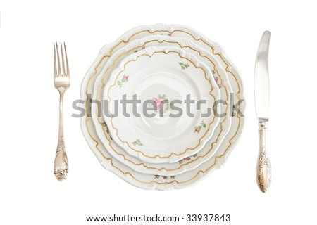 Dinner set with three plates, knife and fork isolated - stock photo