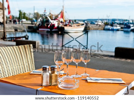 Dinner setting at harborside restaurant with sea harbor and yachts in background: moody and romantic. Typical French restaurant in Honfleur, France.