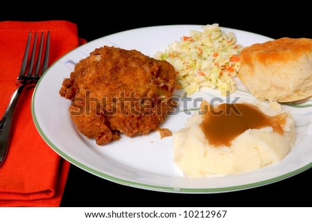 Dinner setting of fried chicken mashed potatoes with brown gravy roll and coleslaw - stock photo