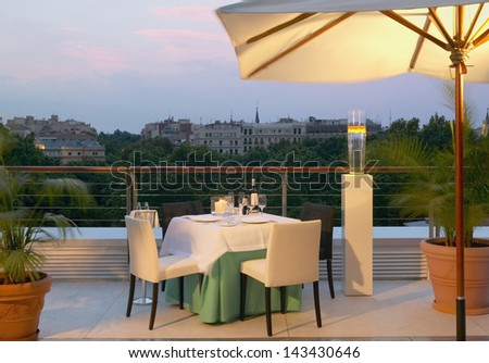 Dinner table for two on the roof with Madrid view background at evening vertical - stock photo
