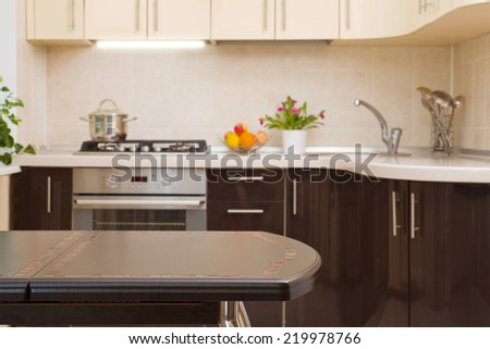 Dinner table on blurred kitchen interior background