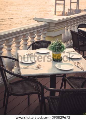 dinner table with artificial flower,plate,fork,spoon ,knife set beside river in color effect - stock photo
