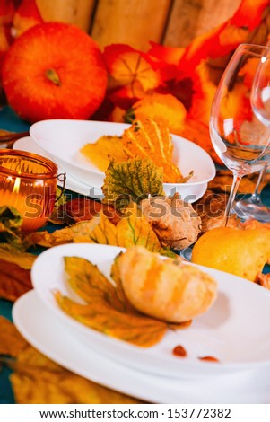 Dinner table with autumn decoration. - stock photo
