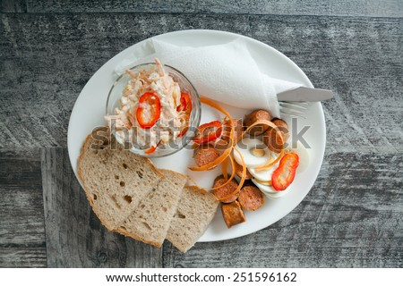 Dinner with fresh vegetable salad, sausages and eggs - stock photo