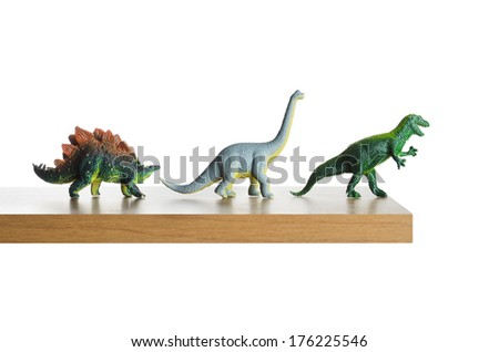 Dinosaurs figurines placed together on a ledge  - stock photo