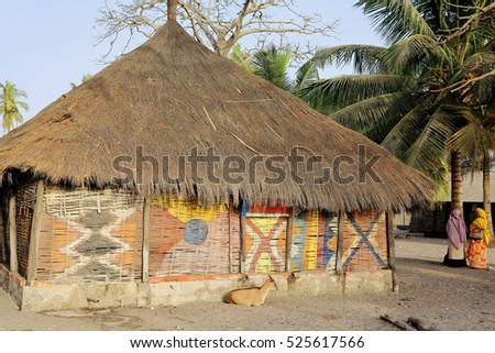 Diola people.s thatch-roofed rural townhouse with palm-matted walls decorated of traditional African motifs in the village of Carabane island at the Casamance river estuary. Ziguinchor prov.-Senegal.