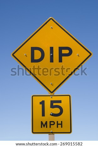 dip 15 mph road sign with blue sky background