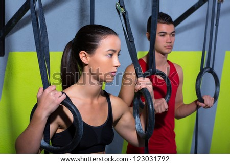 dip ring man and woman relaxed after workout at gym dipping exercise - stock photo