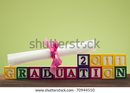 """Diploma tied with a ribbon, the text of the wooden blocks """"Graduation 2011"""". - stock photo"""