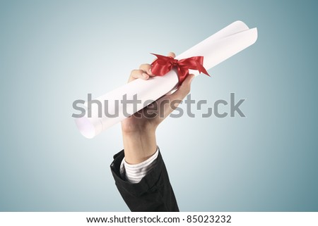 Diploma with a red ribbon in hand  on blue background - stock photo