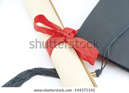 Diploma with red ribbon and black graduation cap on white background with copy space. Macro with shallow dof. - stock photo