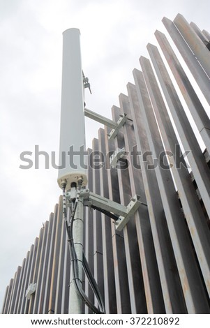 Dipole antenna for telecommunications contrasting white sky background. - stock photo
