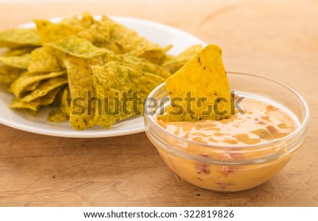 Dipping spicy jalapeno tortilla chips in creamy chili con queso dip in clear glass bowl.