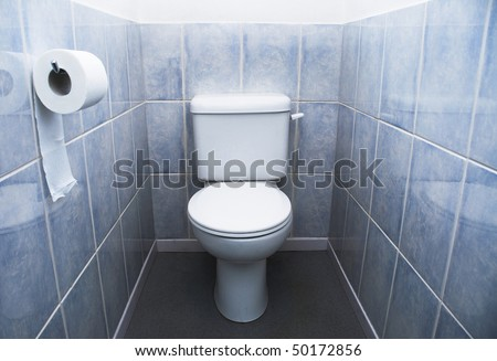Direct, head-on shot of closed-lidded toilet with hanging toilet roll and aqua blue tiles - stock photo