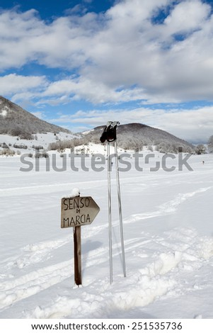 Direction sign and ski poles in the snow on country-cross ski slope. Abruzzi, Italy. - stock photo