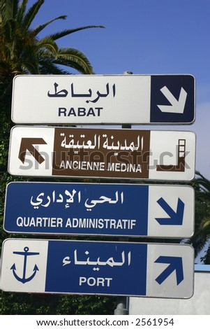Direction sign in Arabic and French in the port city of Assilah in Morocco with palms in the background - stock photo