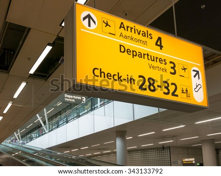 Direction signs and escalators in terminal of Schiphol Amsterdam Airport, Netherlands