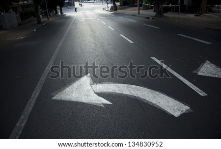 Directional arrow pointing left on an empty street in Tel-Aviv, Israel. Defocused in the background a man is crossing the street. Shot at dawn. - stock photo