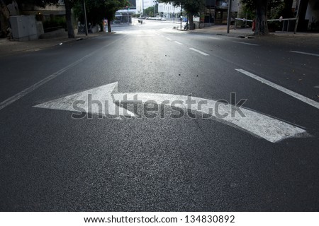 Directional arrow pointing left on an empty street in Tel Aviv, Israel. Wide angle. Shot at dawn. - stock photo