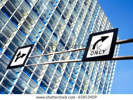 Directional arrow road signs against a glass office building. - stock photo