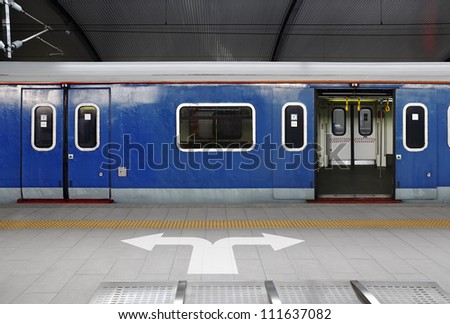 Directional arrow symbol on a train station platform to the sliding mechanical doors of a wet blue color commuter coach. - stock photo