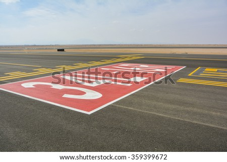 Directional sign markings and landing lights on the tarmac of runway at a commercial airport