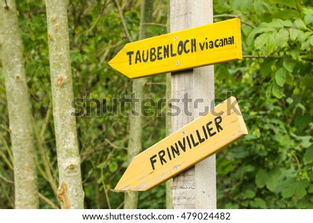 Directions sign. Frinvillier, is a village in the Canton of Bern, Swiss. Taubenloch, is a gorge located in the Canton of Bern, Swiss.