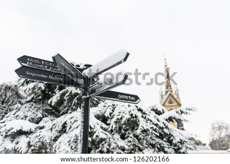 Directions sign in Hyde Park, with Albert Memorial in the background after three days of blizzards. - stock photo